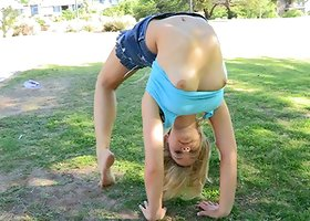 A flexible blonde girl shows her pussy in a park